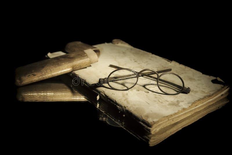 Vidros velhos mesmos dos olhos dos espetáculos do close up com a caixa de madeira no livro aberto muito velho que encontra-se no  imagem de stock