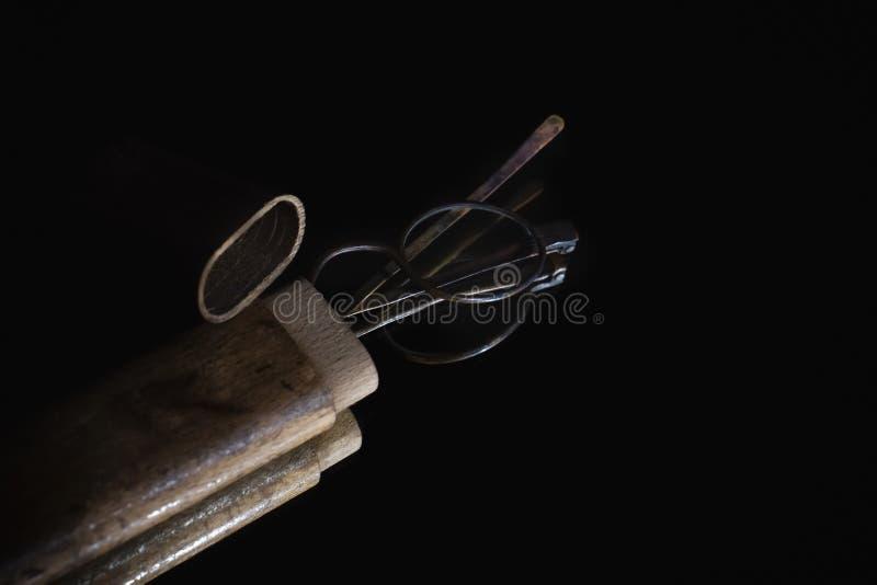 Vidros velhos mesmos dos olhos dos espetáculos do close up na caixa de madeira que encontra-se no espelho para a reflexão imagens de stock