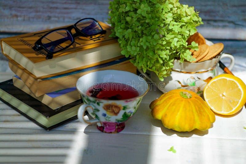 Vidros vermelhos do chá e de leitura na tabela em uma casa acolhedor fotografia de stock