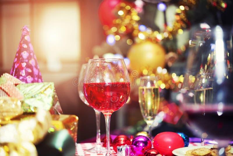 Vidros vermelhos do champanhe na tabela com caixas de presente e accesso do partido imagens de stock