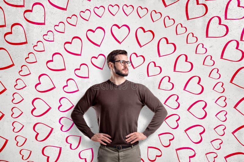 Vidros vestindo consideráveis do homem novo, estando com mãos na cintura, olhando afastado, na parede com teste padrão circular d imagens de stock