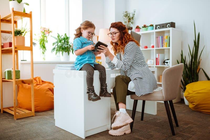 Vidros vestindo da filha engraçada usando a calculadora no escritório da mamã fotos de stock