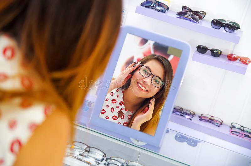 Vidros vestindo da jovem mulher bonita na loja ótica e vista no espelho como olha, em um fundo borrado fotografia de stock royalty free
