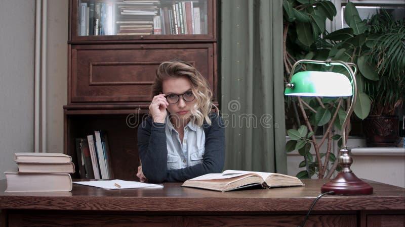 Vidros vestindo da jovem mulher bonita séria que olham fixamente na câmera e que friccionam suas mãos em seu local de trabalho imagem de stock royalty free