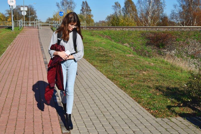 Vidros vestindo da menina adolescente e rua de passeio das calças de brim fotos de stock royalty free