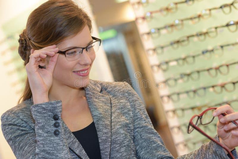Vidros vestindo da mulher bonita do retrato na loja do ótico fotos de stock royalty free