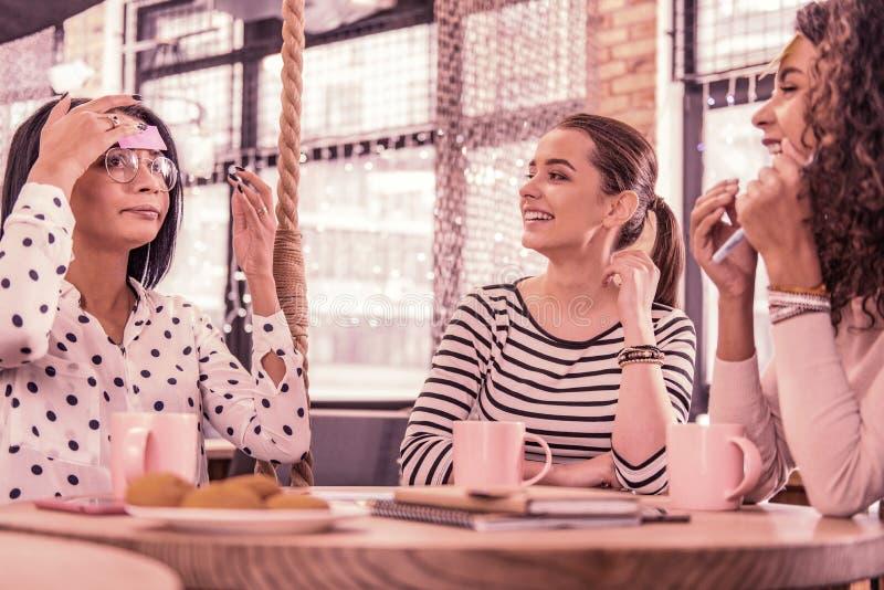 Vidros vestindo da mulher e blusa manchada que explicam a palavra para seus amigos fotos de stock