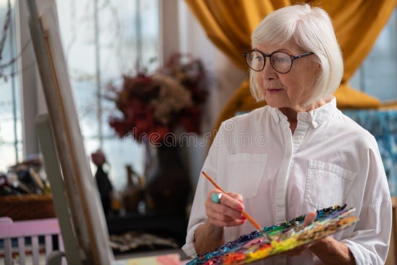 Vidros vestindo da mulher que guardam a paleta de cores e a escova fotos de stock