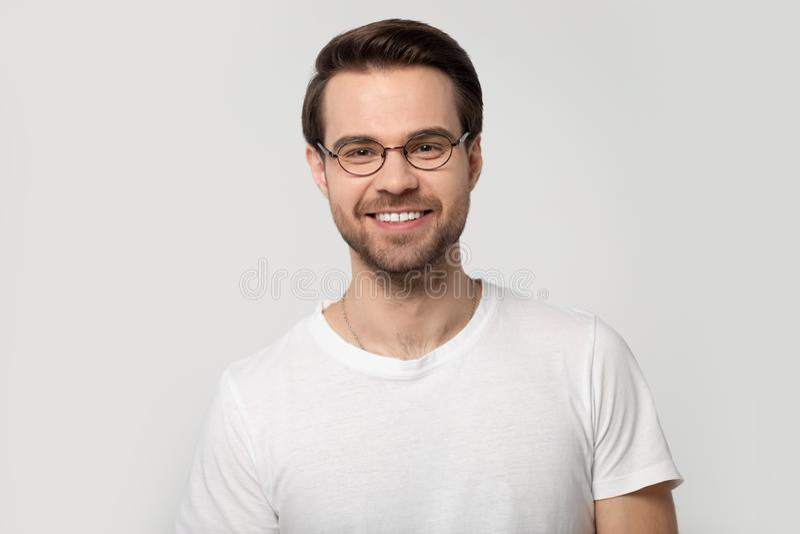 Vidros vestindo de sorriso do homem do retrato do Headshot no fundo cinzento fotografia de stock royalty free