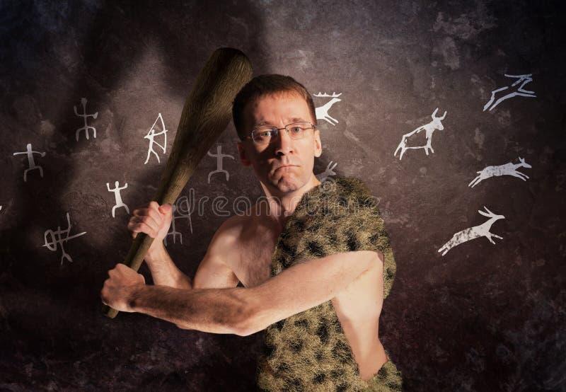 Vidros vestindo de um homem moderno na roupa primitiva com uma clava em sua mão fotografia de stock royalty free