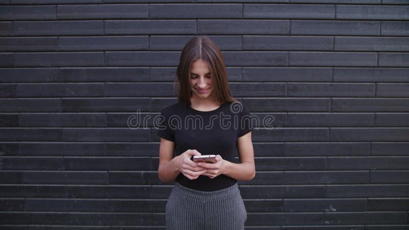 Vidros vestindo de uma jovem senhora atrativa usando um telefone contra um fundo da parede de tijolo Tiro do close-up foto de stock royalty free
