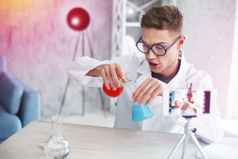 Vidros vestindo do estudante esperto que derramam líquidos coloridos nos tubos de ensaio fotos de stock royalty free