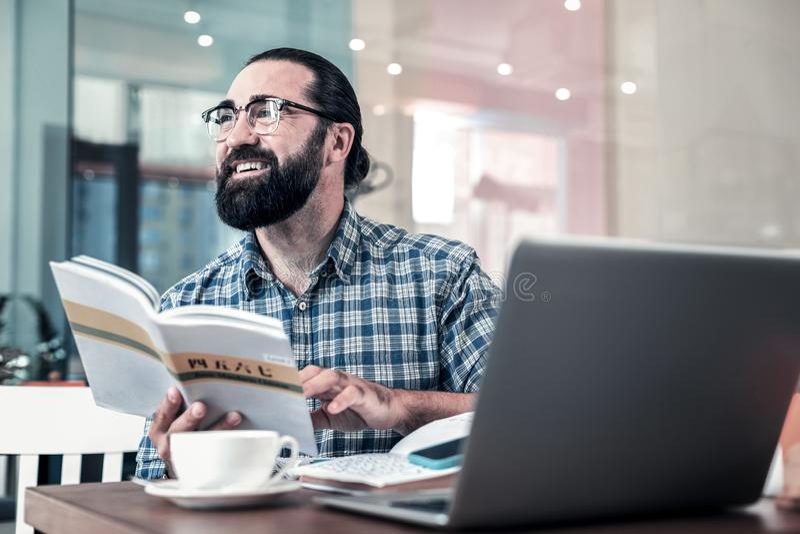 Vidros vestindo do homem de negócios que sentam-se na padaria e que estudam o chinês imagem de stock