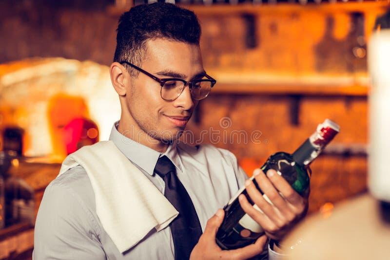 Vidros vestindo do homem que olham a garrafa do vinho francês fotos de stock