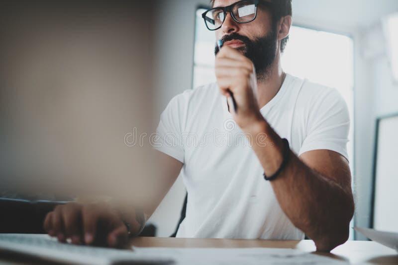 Vidros vestindo do olho do colega de trabalho farpado pensativo e trabalho no estúdio-escritório moderno do sótão Fundo borrado h foto de stock