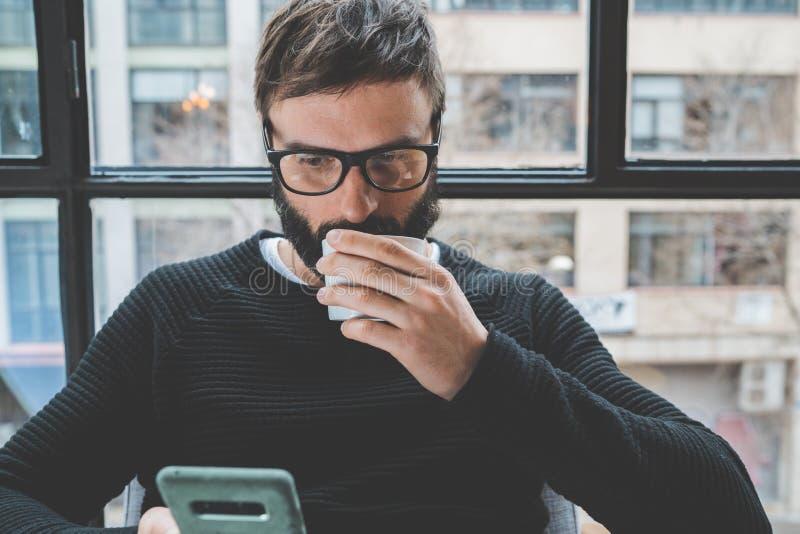 Vidros vestindo do olho do homem farpado considerável e café bebendo ao descansar em casa Homem que usa o smartphone móvel para fotos de stock royalty free