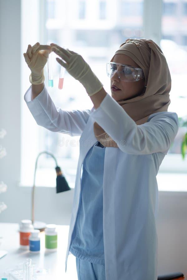Vidros vestindo do químico fêmea novo que estudam líquidos químicos imagem de stock royalty free