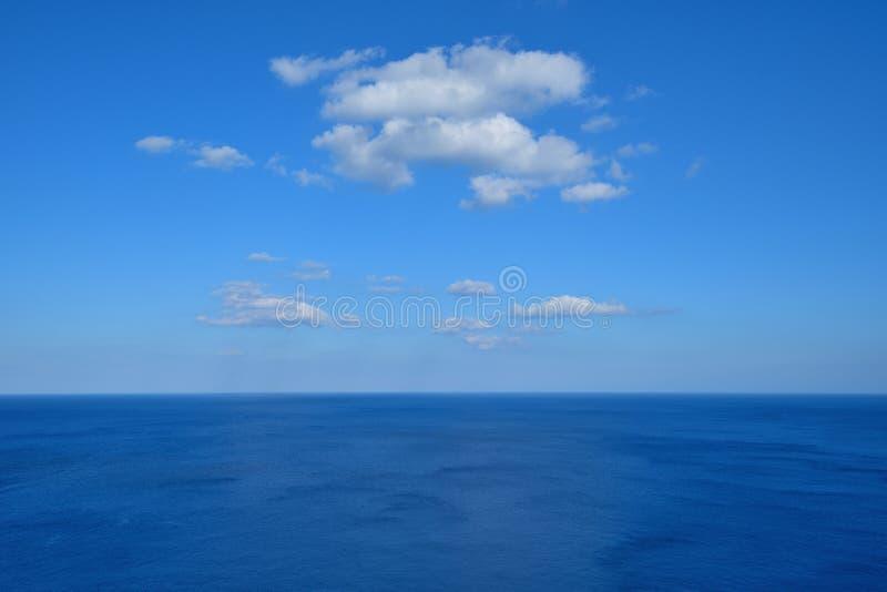 Vidsträckt djupblått hav med moln arkivbild