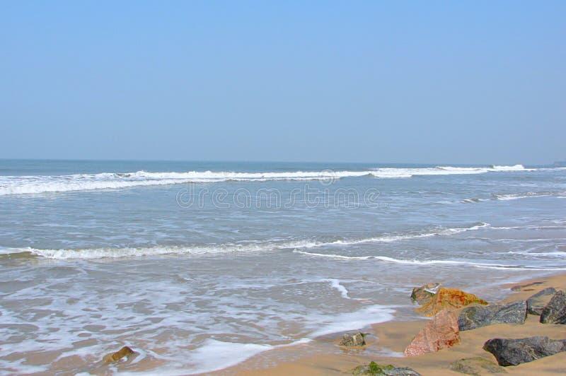 Vidsträckta tysta Serene Ocean med Rocky Beach - den Payyambalam stranden, Kannur, Kerala, Indien royaltyfria foton