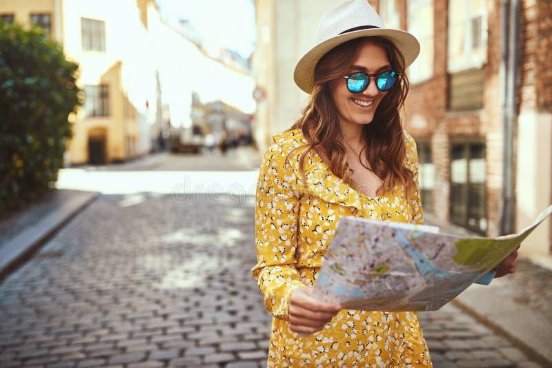 Vie d'esplorazione sorridenti della città del ciottolo della giovane donna con un mA immagini stock