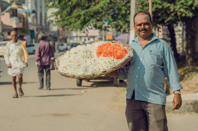 Vie dans la rue et homme avec le plateau énorme des fleurs pour le puja indien dessus images libres de droits
