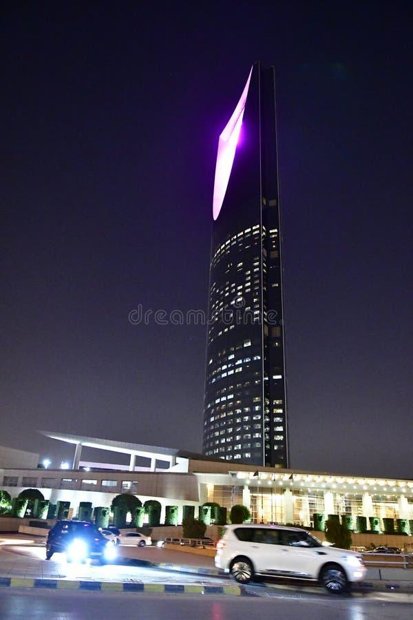 Vie della città alla notte con le luci sulle costruzioni moderne alte immagine stock