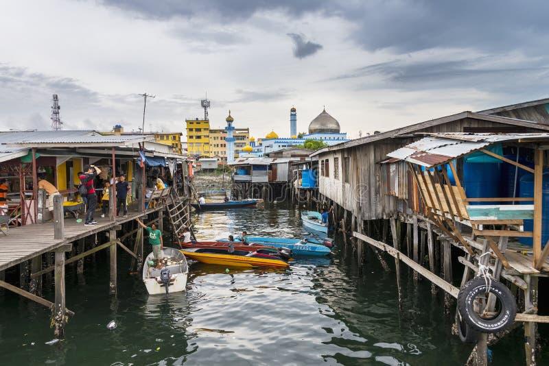 Vie rurale sur les maisons en bois d'échasse au port de pêche avec la mosquée voisine dans Sabah, Malaisie image stock