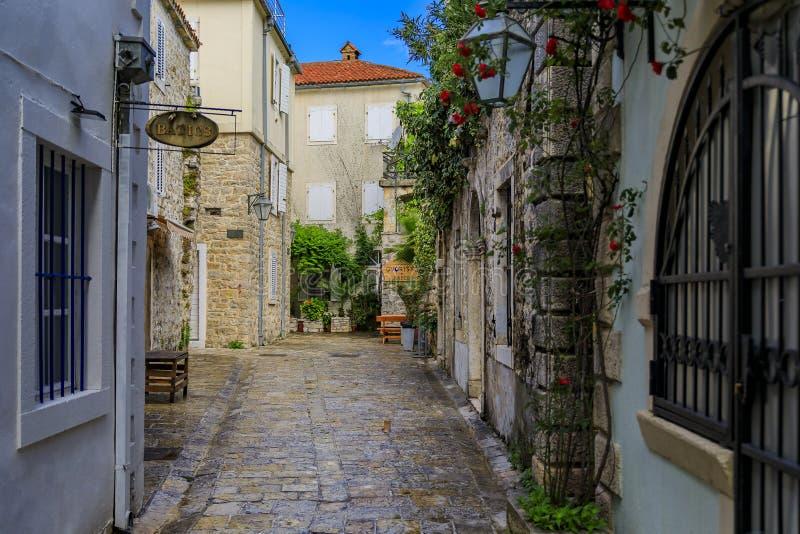 Vie strette pittoresche di vecchia città in Budua Montenegro nei Balcani sul mare adriatico immagini stock