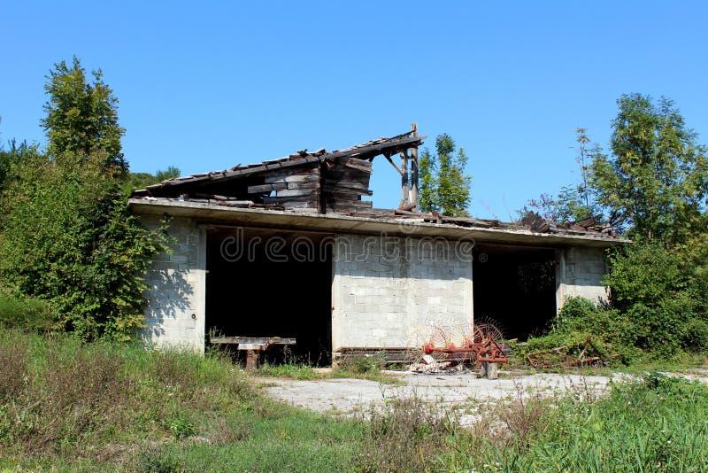 Vieil équipement agricole de ferme sous la forme de foin partiellement rouillé Turner et de chariot devant le garage non fini aba image libre de droits