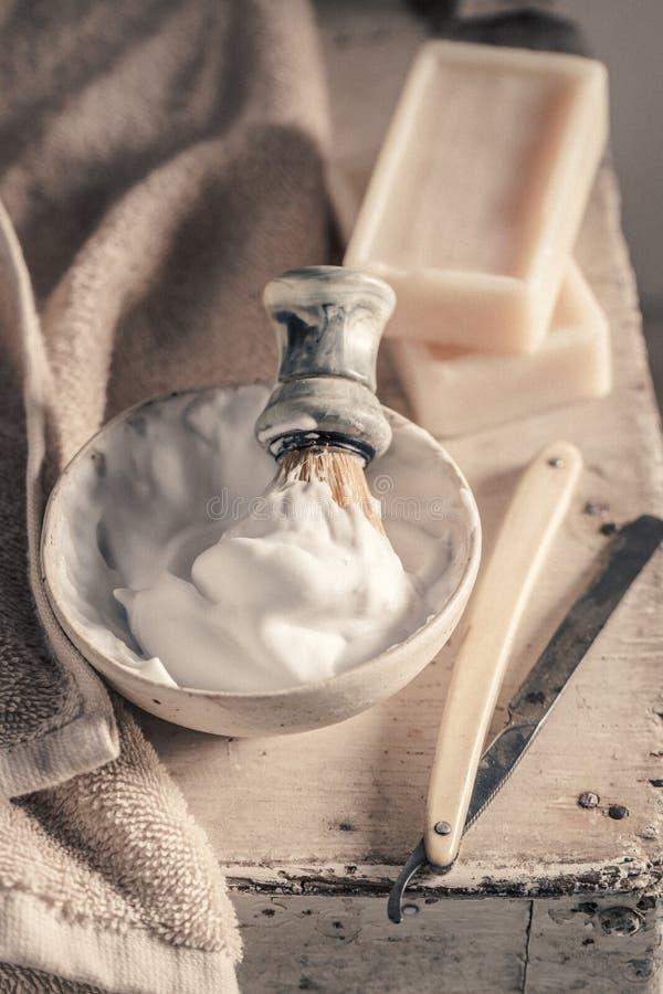 Vieil équipement de coiffeur avec du savon, le rasoir et la brosse gris photographie stock