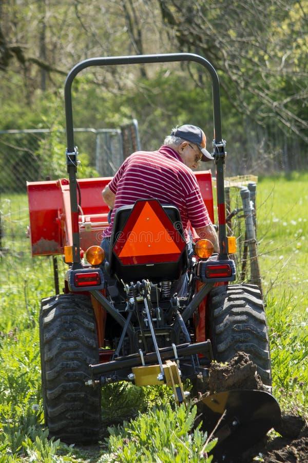 Vieil agriculteur Plowing His Garden avec une charrue inférieure simple photographie stock