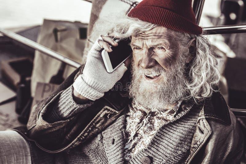 Vieil almsman trouvant le nouveau téléphone et décidant d'appeler à quelqu'un images libres de droits