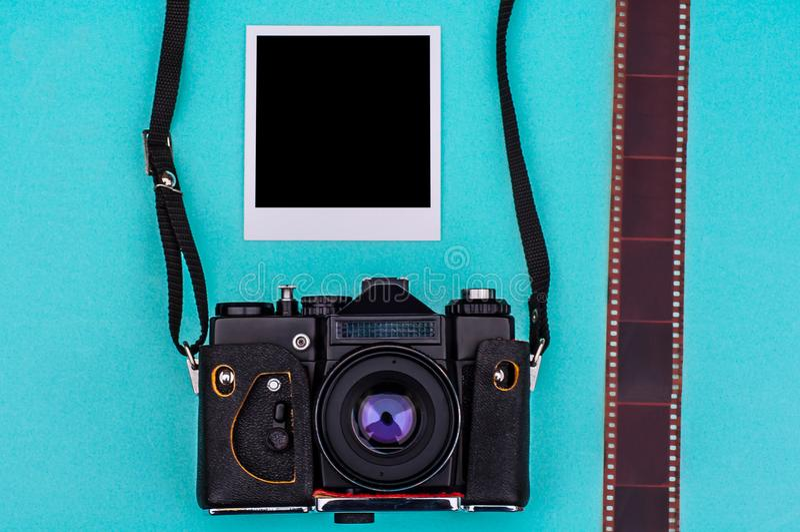 Vieil appareil-photo de film et photographies instantanées avec l'espace vide sur le fond cyan concept de course images stock