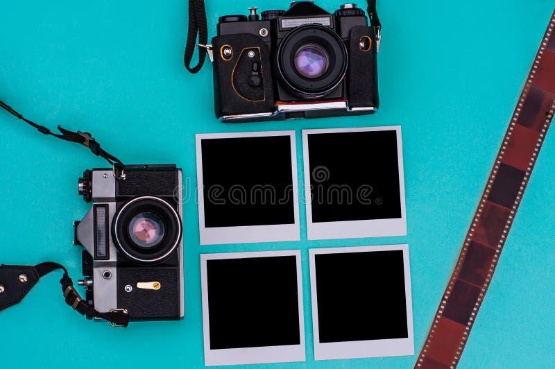 Vieil appareil-photo de film et photographies instantanées avec l'espace vide sur le fond cyan concept de course photographie stock libre de droits