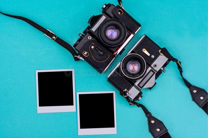 Vieil appareil-photo de film et photographies instantanées avec l'espace vide sur le fond cyan concept de course images libres de droits