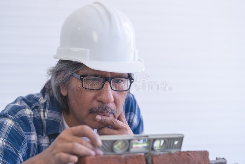 Vieil artisan de constructeur nivelant le mur de briques image libre de droits