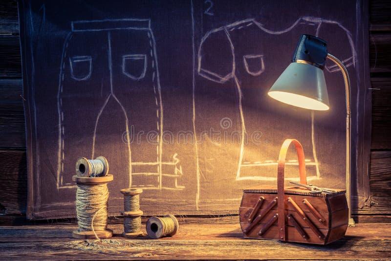 Vieil atelier de tailleur avec les ciseaux, le tissu et la boîte en bois illustration libre de droits