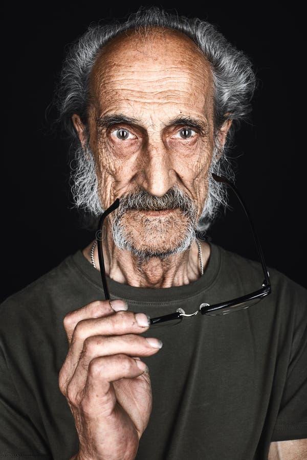 Vieil auteur expérimenté tenant des verres et regardant la caméra photos stock