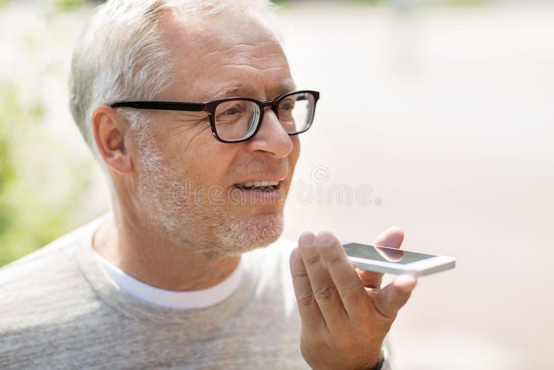 Vieil homme à l'aide de l'enregistreur de commande de voix sur le smartphone photos libres de droits