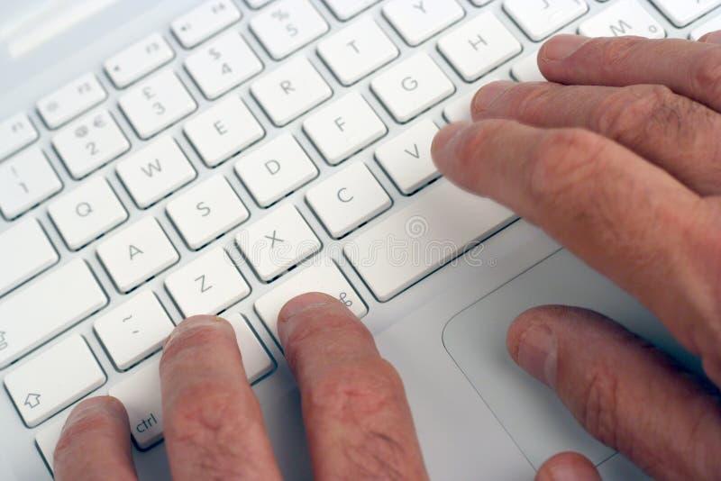Vieil homme à l'aide de l'ordinateur portatif photographie stock libre de droits