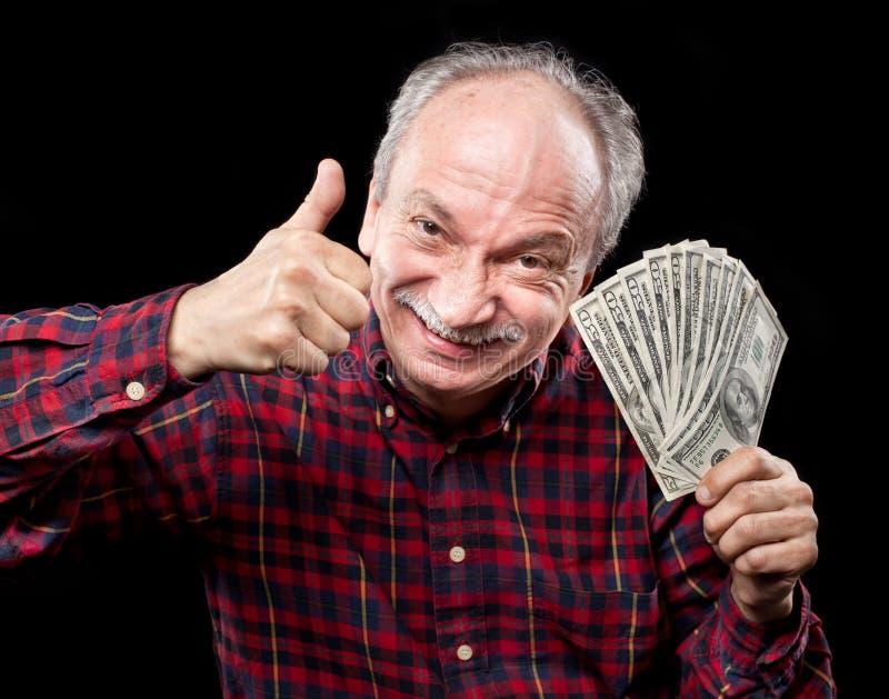 Vieil homme affichant le ventilateur de l'argent image stock