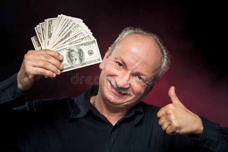 Vieil homme affichant le ventilateur de l'argent photographie stock libre de droits