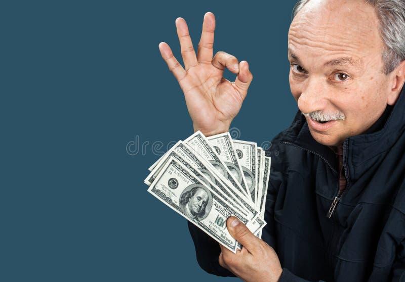 Vieil homme affichant le ventilateur de l'argent photos stock