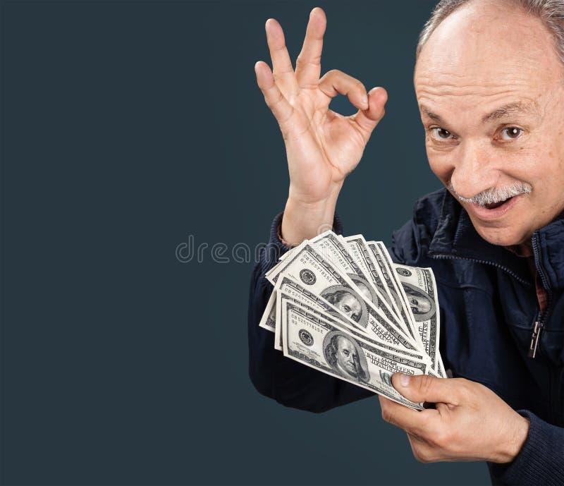 Vieil homme affichant le ventilateur de l'argent photo stock