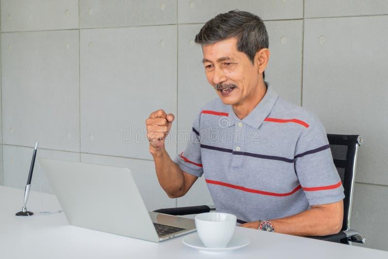 Vieil homme asiatique Réjouissez-vous, soulevez la main droite de poing Se reposer sur le regard de chaise à l'écran d'ordinateur photographie stock