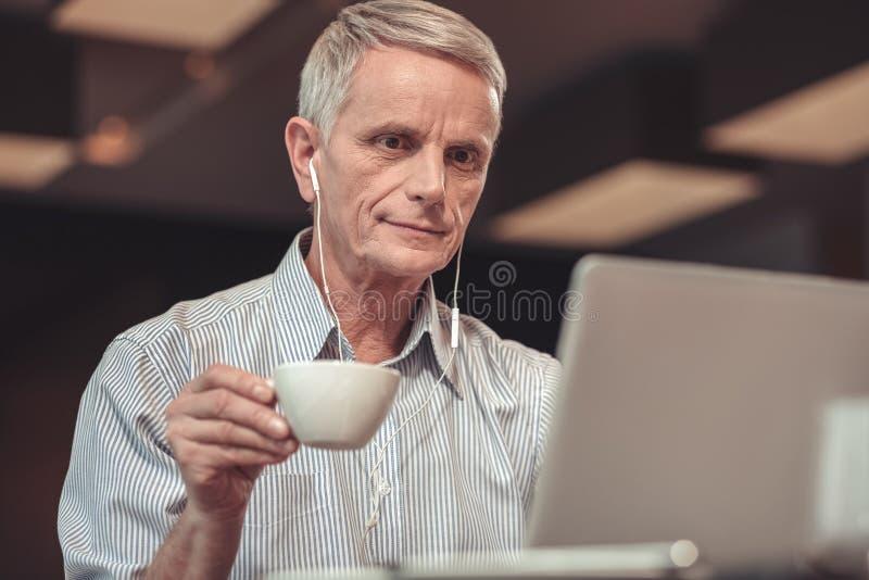 Vieil homme attentif écoutant la musique dans un restaurant image libre de droits