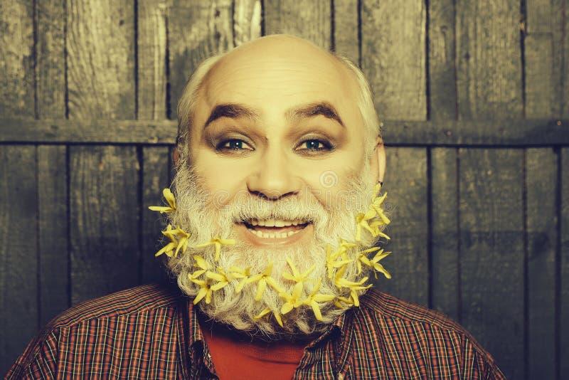 Vieil homme avec des fleurs dans la barbe photographie stock