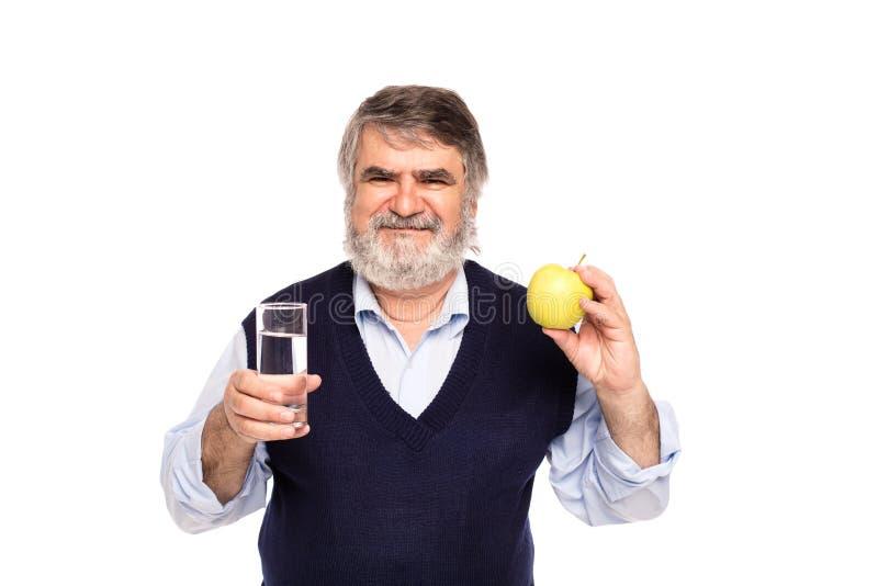 Vieil homme avec l'eau et la pomme image libre de droits