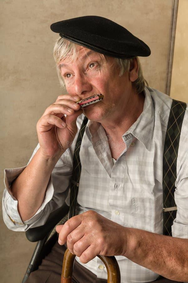 Vieil homme avec l'harmonica images libres de droits