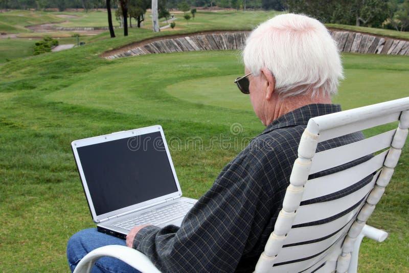 Vieil homme avec l'ordinateur portatif au terrain de golf photo stock